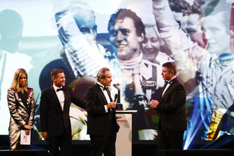 Jacky Ickx accepts a Gregor Grant Award on stage from Tom Kristensen