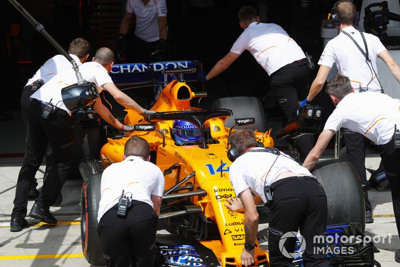 Los mecánicos regresan a Fernando Alonso, McLaren MCL33, al garaje.
