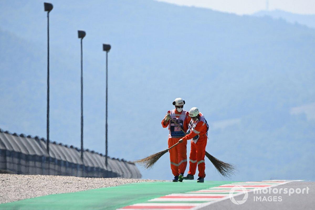 Los oficiales de pista barren el circuito