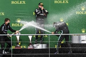 Valtteri Bottas, Mercedes-AMG F1, 2nd position, and Lewis Hamilton, Mercedes-AMG F1, 1st position, celebrate with their team mate on the podium