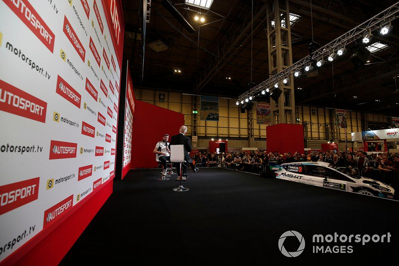 Presenter Alan Hyde interviews Seb Morris on the Autosport stage in front of a large crowd