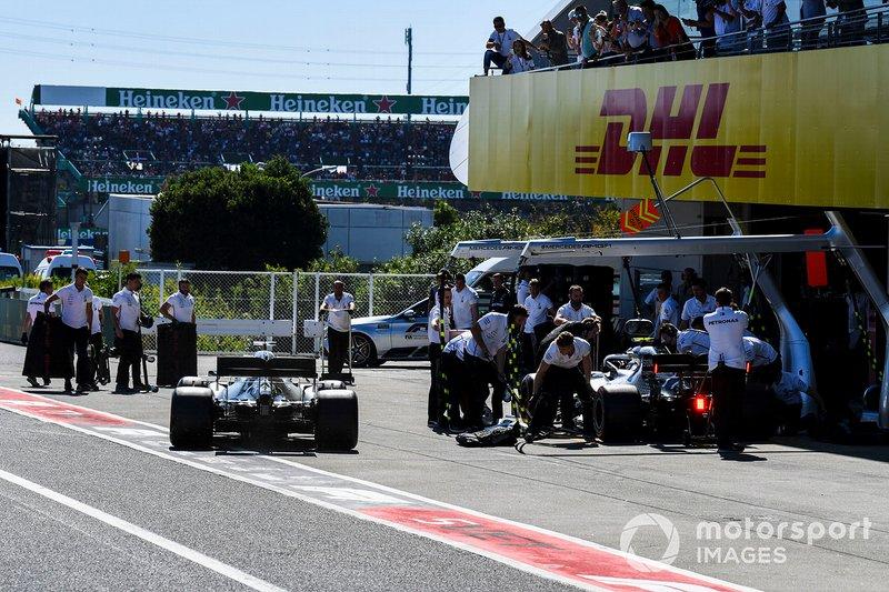 Valtteri Bottas, Mercedes AMG W10, and Lewis Hamilton, Mercedes AMG F1 W10, in the pit lane