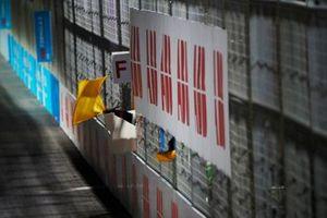 Un commissaire secoue le drapeau jaune