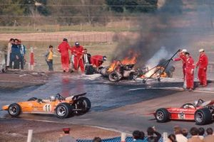 Bruce McLaren, McLaren M14A Ford and Mario Andretti, March 701 Ford drive past the flame engulfed cars of Jacky Ickx and Jackie Oliver