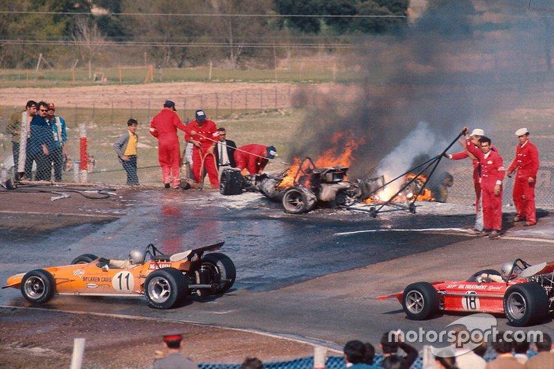 Bruce McLaren, McLaren M14A Ford ve Mario Andretti, March 701 Ford, Jacky Ickx ve Jackie Oliver'ın yanan araçlarının yanından geçiyor