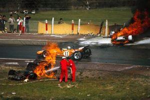 Bruce McLaren, McLaren M14A Ford, conduce entre el ardiente BRM P153 de Jackie Oliver y el Ferrari 312B de Jacky Ickx mientras los oficiales trabajan para extinguir las llamas.