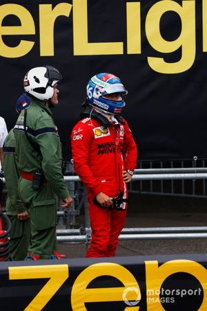 Charles Leclerc, Ferrari, stands behind the barrier after his crash
