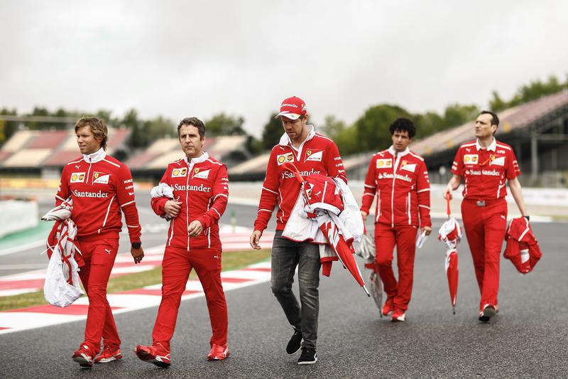 Sebastian Vettel, Ferrari, is accompanied on a track walk by colleagues