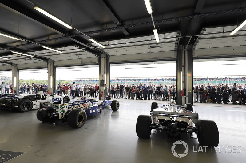Fans view a garage filled with classic Williams F1 machinery