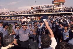 Le vainqueur Jody Scheckter, Wolf Ford entouré par le service de sécurité