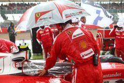 Un mecánico de Ferrari mantener la lluvia fuera de cabina