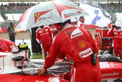 Un mécanicien Ferrari protège le cockpit de l'eau