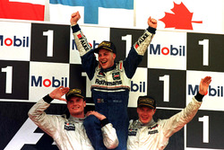 Jacques Villeneuve, Williams is lifted shoulder high by Mika Hakkinnen, McLaren and David Coulthard,