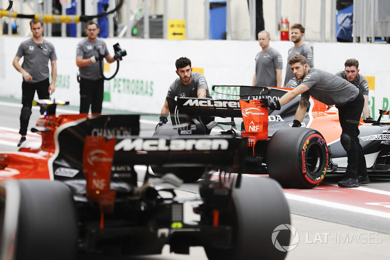 Engineers return Fernando Alonso, McLaren MCL32, to the garage