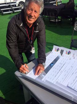 Mario Andretti, Justin Wilson posterini imzalıyor