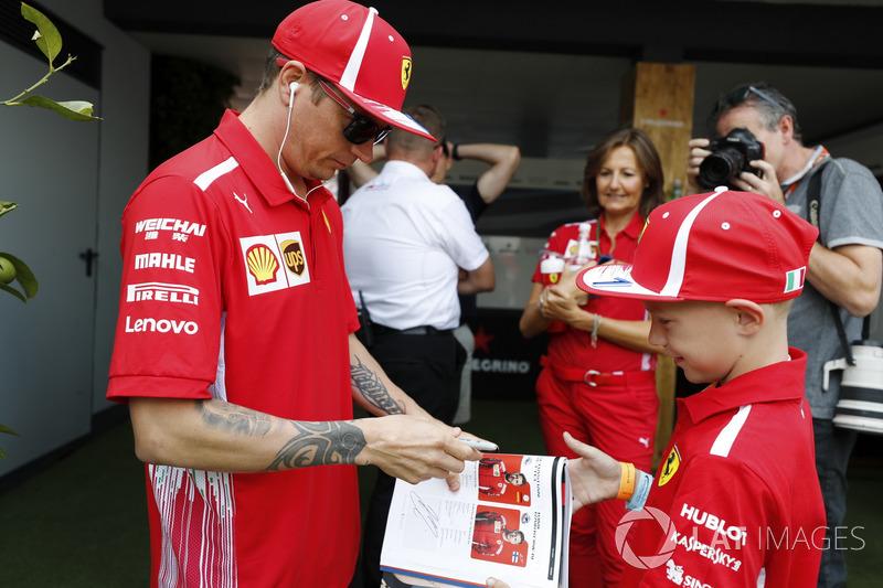 Kimi Raikkonen, Ferrari, signs an autograph for a young fan