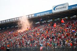 An orange smoke flare is ignited in the crowd