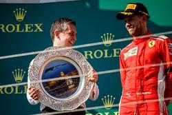 Mercedes AMG F1 team member celebrates on podium and Sebastian Vettel, Ferrari
