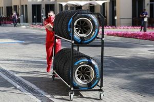 A Ferrari mechanic pushes a trolley of tyres in the paddock