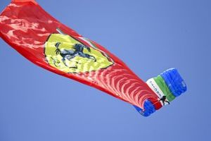 A Ferrari flag is trailed by a parachutist