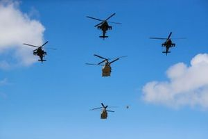 A trio of AH-64A Apaches and a pair of CH-47D Chinooks of the US Army fly over the grid prior to the start