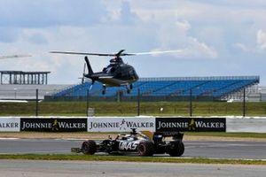 Romain Grosjean, Haas F1 Team VF-19, passes a landing Agusta A109E Helicopter