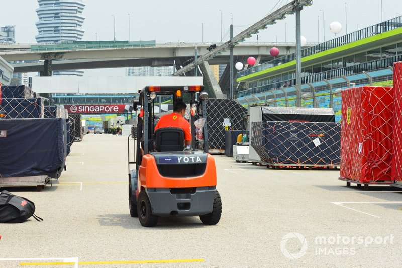 A forklift truck negotiates freight belonging to Ferrari and Red Bull on the pit straight