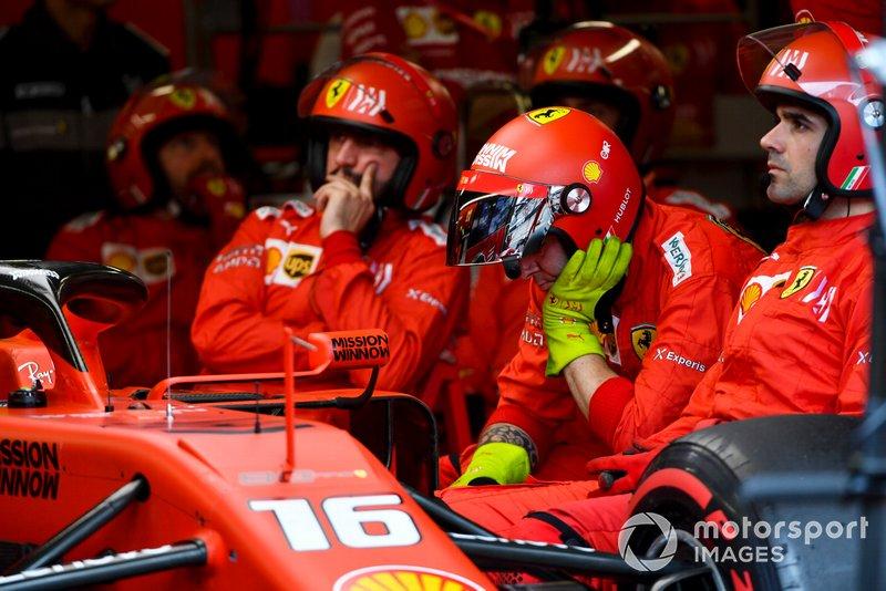 El mecánico se sentó en el garaje junto al coche retirado de Charles Leclerc, Ferrari SF90.