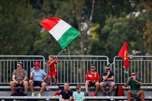 A young fan waves an Italian flag from a grandstand
