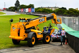 Marshals remove the car of Daniil Kvyat, Toro Rosso STR14, from the circuit with a JCB