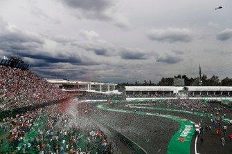 Los aficionados invaden la pista en el podio después de la carrera