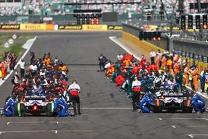 Mechanics make final preparations on the grid prior to the start