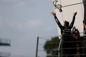 Lewis Hamilton, Mercedes, 1st position, tosses his trophy in the air in celebration on the podium