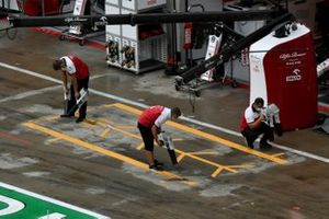 Alfa Romeo Racing team dry the pit lane