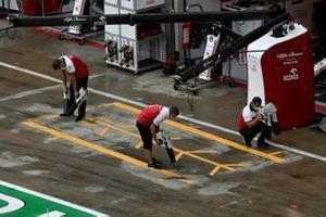Механики Alfa Romeo Racing высушивают асфальт перед своими боксами