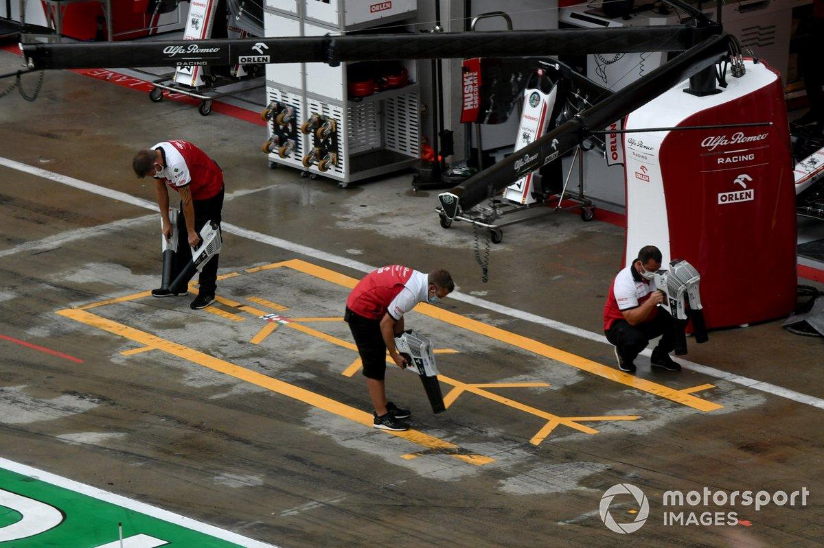 Alfa Romeo Racing team dry the pit lane
