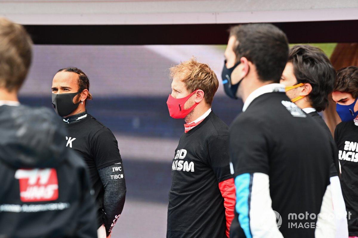 Los otros pilotos se reúnen alrededor de los trofeos antes del comienzo en apoyo de la campaña para el fin del racismo