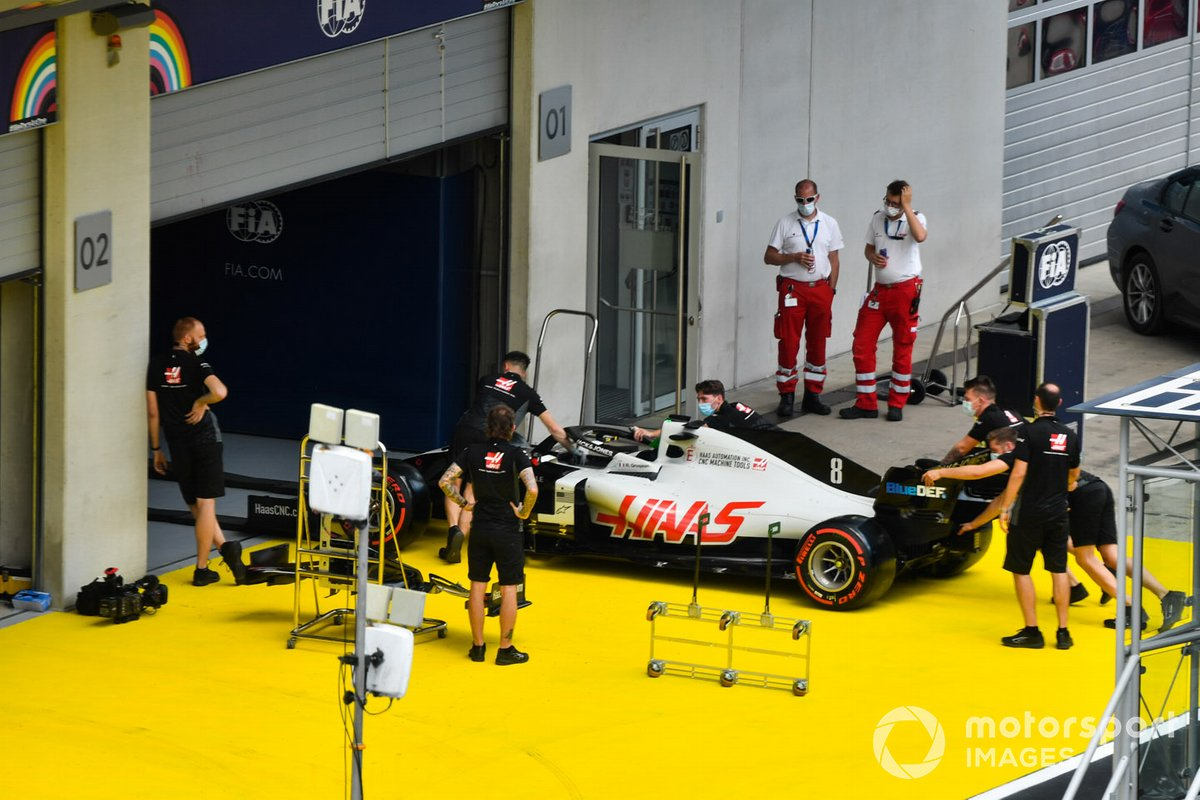 The Romain Grosjean Haas VF-20 is pushed into the FIA technical inspection pit garage