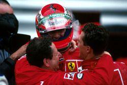 Race winner Michael Schumacher, Ferrari F310B and Jean Todt embrace Eddie Irvine, Ferrari F310B
