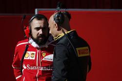 A Ferrari team member talks to a counterpart at Pirelli