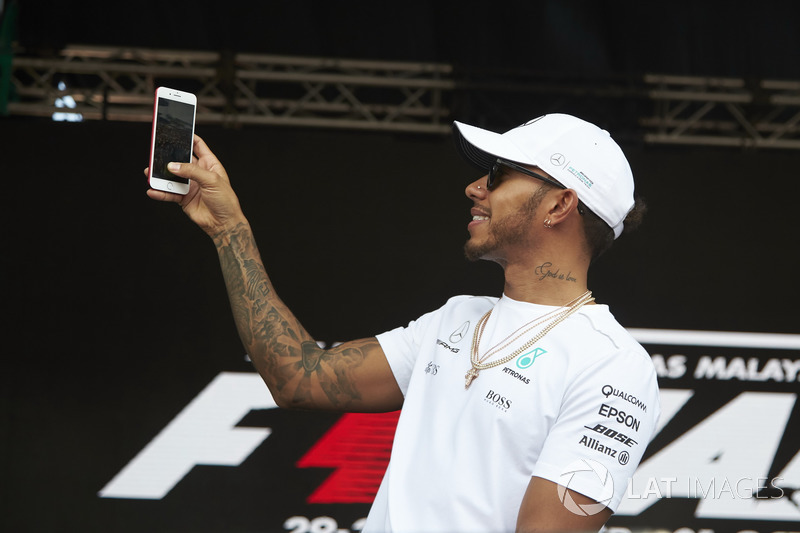 Lewis Hamilton, Mercedes AMG F1, uses his phone on stage