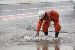 Un marshal controlla un tombino traboccante di acqua piovana
