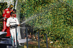 Le deuxième, Lewis Hamilton, Mercedes AMG F1, le vainqueur Sebastian Vettel, Ferrari, et le troisième, Kimi Raikkonen, Ferrari, sur le podium avec du champagne