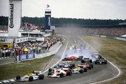 Nelson Piquet, Williams FW11 Honda, leidt bij de start terwijl Stefan Johansson, Ferrari F1/86, tegen Teo Fabi, Benetton B186 BMW aan spint na een aanrijding met Philippe Alliot, Ligier JS27 Renault