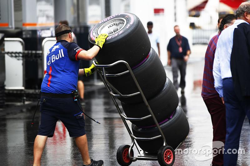 Un mécanicien Toro Rosso avec une pile de pneus