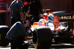 A Pirelli engineer checks a tyre on the Fernando Alonso McLaren MCL32