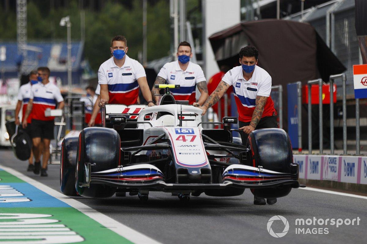 Los mecánicos de Haas F1 empujan el coche de Mick Schumacher, Haas VF-21, por el pitlane