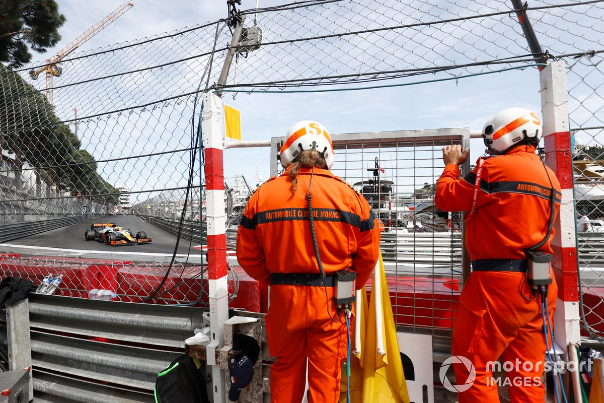 Oficiales de pista ven a Daniel Ricciardo, McLaren MCL35M, pasar