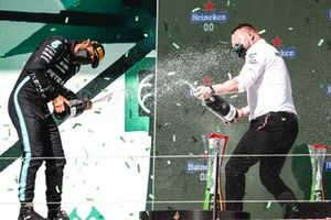 Lewis Hamilton, Mercedes, 1st position, and the Mercedes trophy delegate celebrate on the podium with Champagne