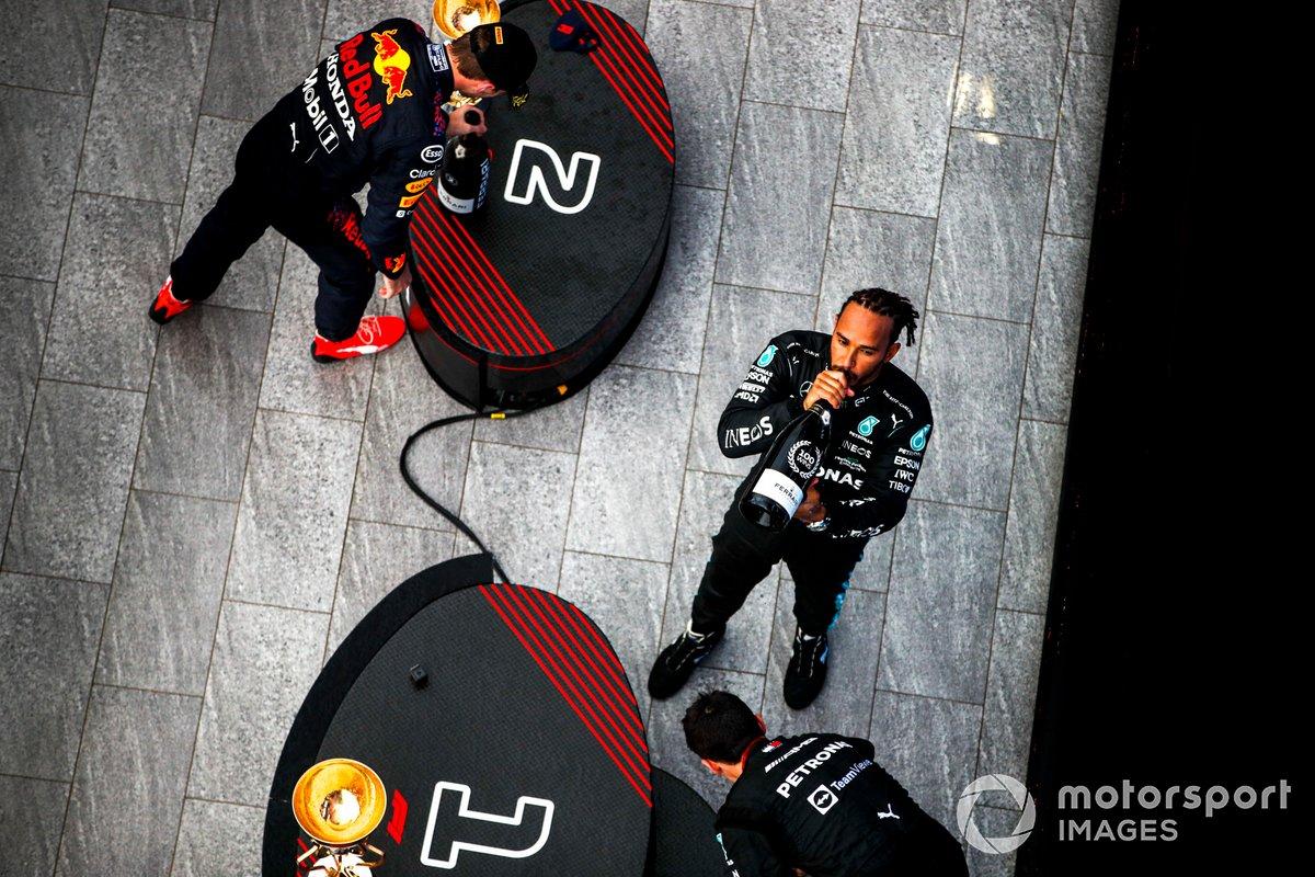 Max Verstappen, Red Bull Racing, 2a posizione, e Lewis Hamilton, Mercedes, 1a posizione, festeggiano con Champagne sul podio